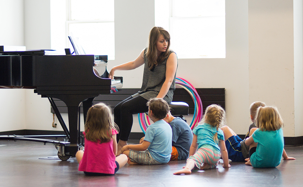 Photo of a Dalcroze class, with the teacher at a piano 和 children sitting on the floor around her
