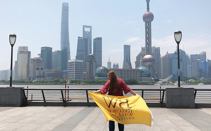 商业 major Gwyn Dubel in 中国 holding a Baldwin Wallace flag in front of a skyline.